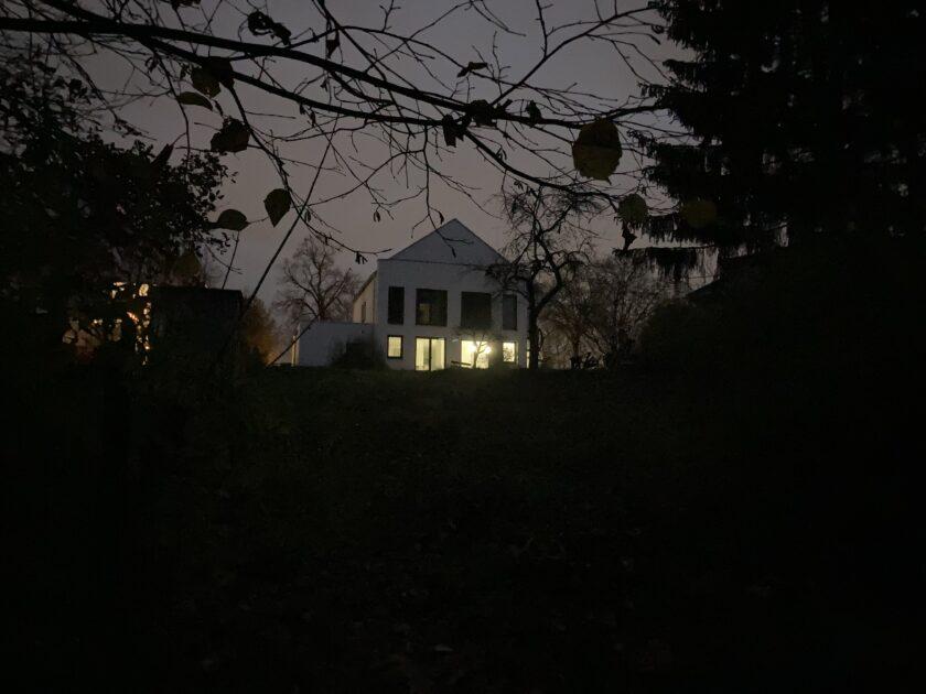 Haus mit erleuchteten Fenstern im Dunkeln
