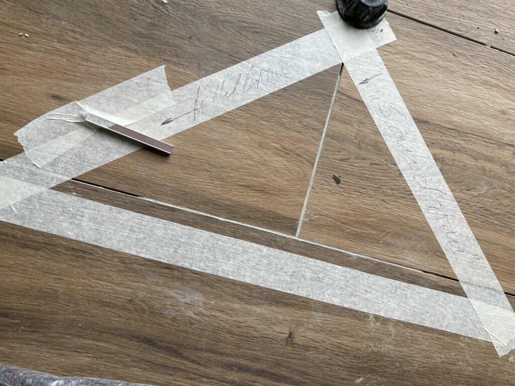 Fliesen in Holzoptik mit Fugenprobe in durch Klebeband gekennzeichnetem Bereich